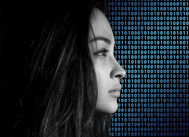 Photo: Female profile over binary codes in background
