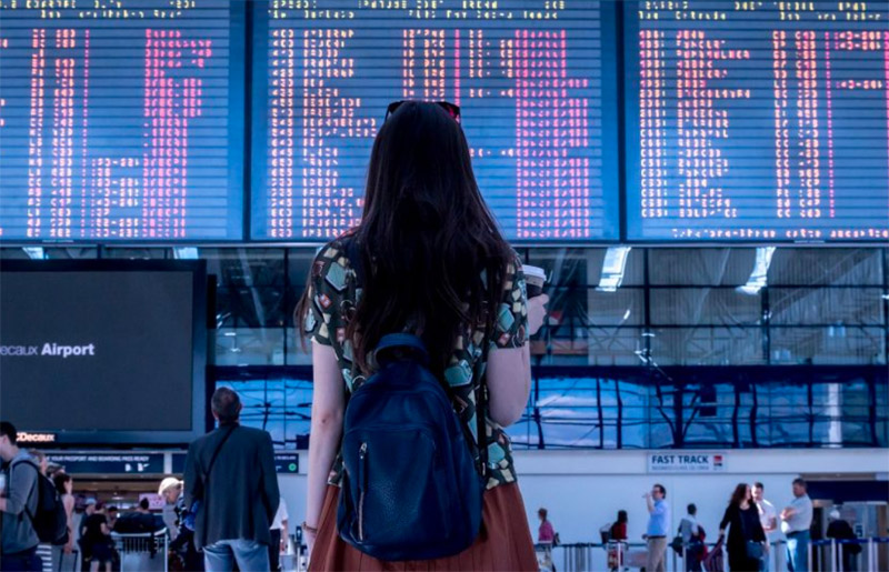 Photo: Asian female in front of airport terminal flipboard