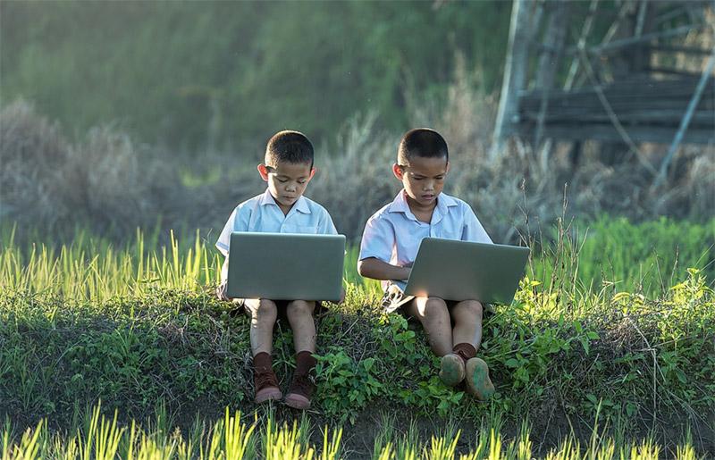 Photo: 2 South East Asian boys on laptops